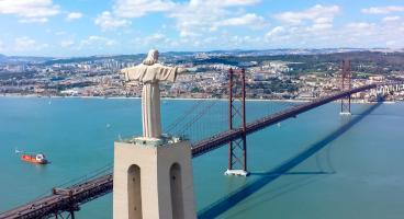 Städtetrip Lissabon: Die Cristo Rei Statue mit ihrer 82 Meter hohen Aussichtsplattform vor der Brücke Ponte 25 de Abril über den Tejo.